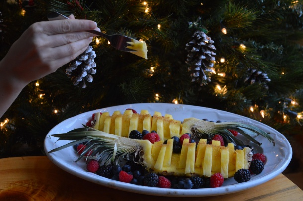 Taking a slice of pineapple in front of the Christmas tree